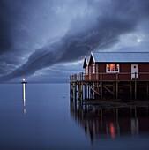 Rorbuer on stilts at dusk with lighthouse, Lofoten Islands, Norway, Scandinavia, Europe