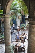 People sitting at tables and musicians playing in courtyard of colonial building built in 1780, Havana, Cuba, West Indies, Central America
