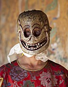 Buddhist monk wearing carved wooden mask in the shape of a skull preparing to take part in traditional dance performance at the Tamshing Phala Choepa Tsechu, near Jakar, Bumthang, Bhutan, Asia