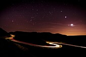 Light trails and stars cape with Venus, Jupiter, Orion and the moon clearly visible above a winding road in the Peak District National Park. Derbyshire, England, United Kingdom, Europe