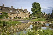 Cottages and footbridge over the River Eye in the Cotswolds village of Lower Slaughter, Gloucestershire, England, United Kingdom, Europe