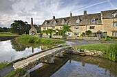 Stone footbridge and cottages at Lower Slaughter in the Cotswolds, Gloucestershire, England, United Kingdom, Europe
