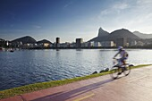 Cyclist on pathway around Botafogo Bay with Christ the Redeemer statue (Cristo Redentor) in the background, Rio de Janeiro, Brazil, South America