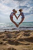 Two young women jumping in the air from the beach in the shape of a heart, 'S Arenal, Palma, Mallorca, Balearic Islands, Spain