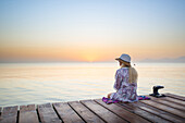 Young blond-haired woman sitting on the end of a long pier in the morning mood, enjoying the view of the sunrise. Playa de Muro beach, Alcudia, Mallorca, Balearic Islands, Spain