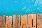 Detailed view from the top view of a wooden pier with turquoise water. Playa de Muro beach, Alcudia, Mallorca, Balearic Islands, Spain