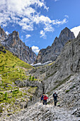 Persons hiking descending from hut Langkofelhuette, Langkofel and Langkofelspitze in background, Friedrich-August-Weg, Langkofel group, Dolomites, UNESCO World Heritage Dolomites, Trentino, Italy