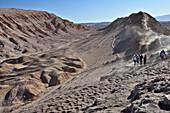group at trekking through desert mountains, Valle de la Luna, Valley of the moon, Atacama desert, National Reserve, Reserva Nacional Los Flamencos, Region de Antofagasta, Andes, Chile, South America