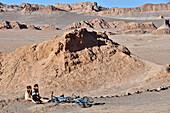 Young woman with bicycles beetween rocks, Valle de la Luna, Valley of the moon, Atacama desert, National Reserve, Reserva Nacional Los Flamencos, Region de Antofagasta, Andes, Chile, South America