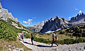 Hikers beneath Tre Cime di Lavaredo towards Altensteintal, Val Pusteria Valley, Sesto, Dolomites, South Tyrol, Veneto, Alto Adige, Three Peaks Nature Park, UNESCO world heritage side, Italy, European Alps, Europe