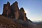 sun appears behind Three Peaks (Drei Zinnen), sun rays, Val Pusteria Valley, Sesto, Dolomites, South Tyrol,Belluno, Veneto, Alto Adige, Three Peaks (Tre Cime di Lavaredo) Nature Park, UNESCO world heritage side, Italy, European Alps, Europe