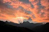 Sunbeams before sunrise behind mountain range Rosengarten, Catinaccio, St. Zyprian, Tiers, Tiers Valley, Nature Park Schlern Rosengarten, Dolomites, South Tyrol, Alto Adige, UNESCO world heritage side, Italy, European Alps, Europe