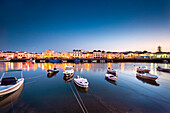View across Rio Gilao towards fishing quarter at twilight, Tavira, Algarve, Portugal