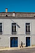 Old man in front of tiled house, Beja, Alentejo, Portugal