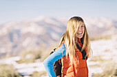 A young woman with blonde hair smiles on a hike in winter.