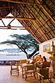 A man and a woman sit in a thatch roof lounge area overlooking an African beach.