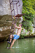 A young man smiles while climbing a ladder on the bank of a river before jumping in.