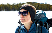 A young women looks towards the West while snowshoeing over a Frozen Daicey Pond in Baxter State Park.