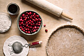 Ingredients for a cranberry tart with an almond and spelt flour crust, maple syrup and powdered sugar.