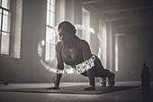 Virtual words circling Black athlete doing push-ups