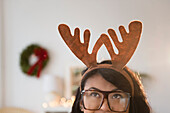 Pacific Islander woman wearing Christmas reindeer horns
