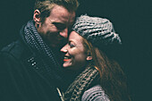 Smiling couple wearing warm clothing hugging