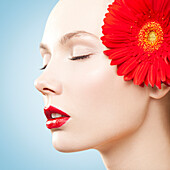 Caucasian woman with red lipstick wearing matching flower