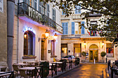 Outdoor patio seating on an illuminated street at dusk, Arles, Provence-Alpes-Cote D'Azur, Bouches-Du-Rhone, France