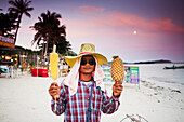 A local vendor selling pineapple and corn on the beach of Chaweng at sunset, Chaweng, Ko Samui, Thailand