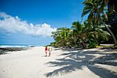 Tourists walking along the beach, Tanna Island, Vanuatu