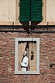 A statue in the window of a brick building, looking out past the curtains, Montepulciano, Tuscany, Italy