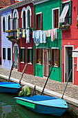 Blue boats sit in front of a row of colourful houses, Burano, Venice, Italy