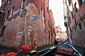 View of buildings along a narrow canal from a gondola, Venice, Italy