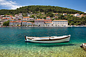 A small boat rests in the tranquil clear water, Pucisca, Island of Brac, Croatia