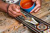 Man painting a traditional Toraja design on piece of wood, Kete Kesu, Toraja Land, South Sulawesi, Indonesia