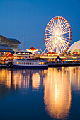 Chicago, Illinois Boat Leaving Navy Pier At Night, Ferris Wheel, Lights Reflected In Water Of Lake Michigan