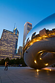 Illinois Chicago Bean Sculpture In Millennium Park At Dusk, City And Buildings Reflected In Modern Metal Public Art, Couple Hug In Plaza