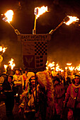 People dressed as American Indians walking in procession for East Hoathly Bonfire Night, East Sussex, England