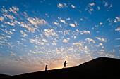 Two young girls running up sand dune at dusk, Dubai, United Arab Emirates