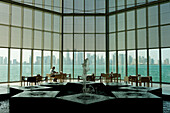 Man and fountain in front of large window in the Museum of Islamic Art, Doha, Qatar