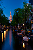 Looking along small canal with the spire of the Zuiderkerk church at the end at dusk, Amsterdam, Holland