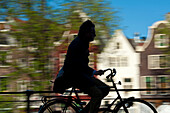 Silhouette of cyclist going past canal and gabled houses, Amsterdam, Holland