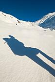 Shadow of walker with rucksack going up snowy slopes of Beinn Respiol, Ardnamurchan peninsula, Highlands, Scotland