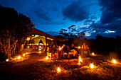 People sitting around fire at dusk in front of dining tent, Ol Pejeta Camp, Ol Pejeta Conservancy, Kenya