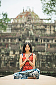 A young woman in meditation on Baphuon Temple is just next to Bayon Wat, built in Eleventh Century by Udayadityavarman II dedicated to the Hindu God Shiva, Angkor, Siem Reap, Cambodia