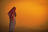 Saudi standing to watch the glowing orange sunset, Taif, Saudi Arabia
