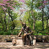 'Statue of a man sitting and reading on a bench in an urban park; New York City, New York, United States of America'