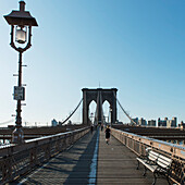 'Runners on a wooden boardwalk on a bridge with bench and lamp post; New York City, New York, United States of America'