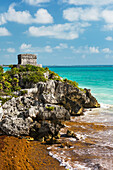 'Ancient Mayan Temple on rock cliff overlooking the ocean with blue sky and clouds; Tulum, Quintana Roo, Mexico'