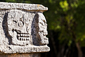 'Close up of Ancient Mayan rock carvings of skulls on edge of building with trees in background; Chichen Itza, Yucatan, Mexico'
